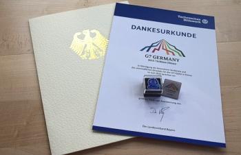 Urkunde und Ansteck-Pins des Landesverbandes Bayern für im Rahmen des G7-Gipfels eingesetzte Helferinnen und Helfer